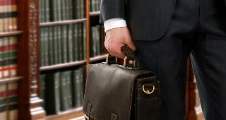 Lawyer holding briefcase in library © sheff/Shutterstock.com