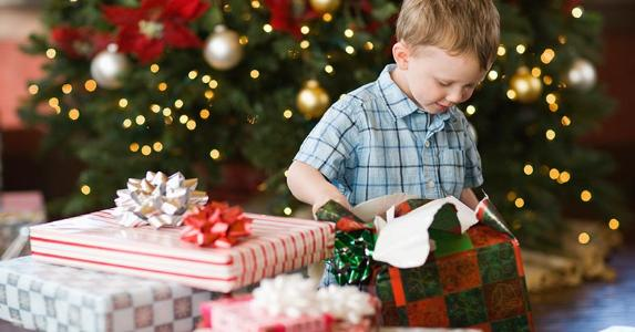 Little boy opening Christmas presents | Mint Imagse/Getty Images