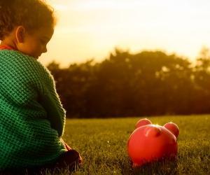 Little girl sitting next to a piggy bank outdoors © iStock