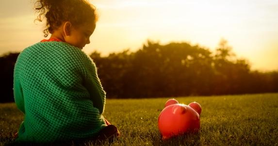 Little girl sitting next to a piggy bank outdoors © iStock