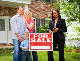 A family and real estate agent in front of house with 'For sale' sign
