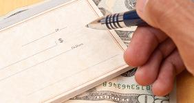 Male hand writing check on money © jcjgphotography/Shutterstock.com