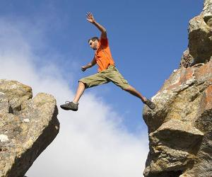 Male rock climber jumping between rocks | Echo/Cultura/Getty Images
