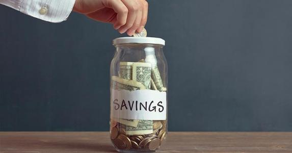 Adding to savings jar | iStock.com/pinstock