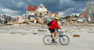 Man biking past homes destroyed by Superstorm Sandy © Paul Lurrie/Shutterstock.com