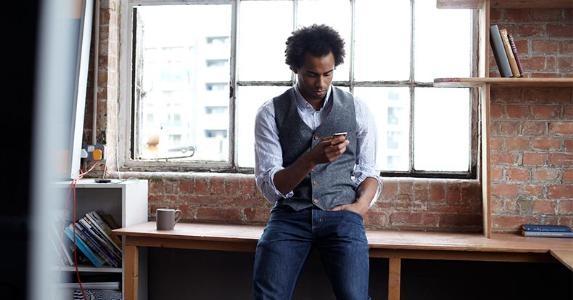Man leaning on desk, looking at phone | Lilly Roadstones/Getty Images