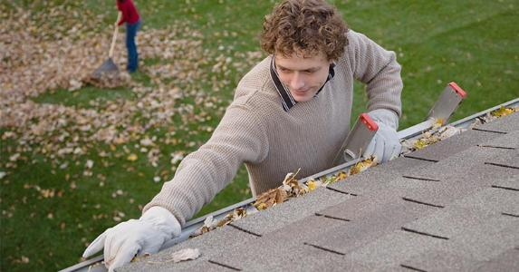 Man cleaning dead leaves from rain gutters | DreamPictures/VStock/Getty Images