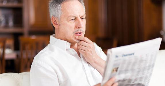 Man reading newspaper © iStock
