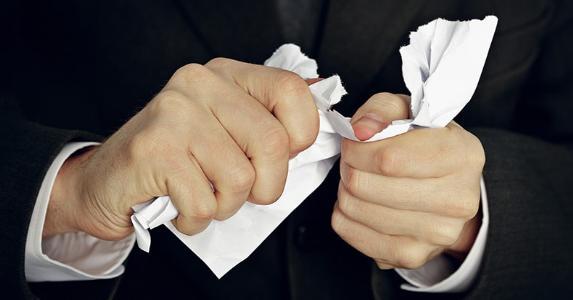 Man crumpling paper in hands © pzAxe/Shutterstock.com