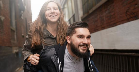 Man giving piggyback ride to his girlfriend | Jeffbergen/E+/Getty Images