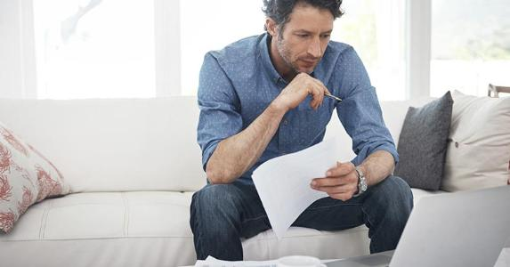 Man going over paperwork at home in living room | iStock.com/shapecharge
