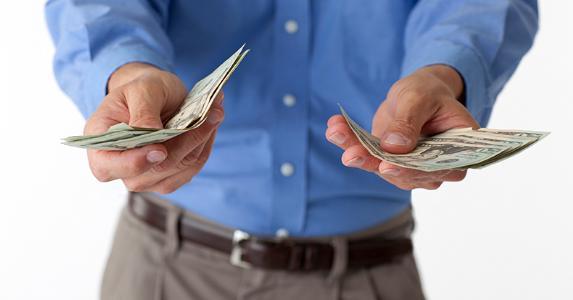 Man holding $20 bills in both hands