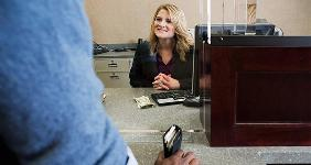 Man at bank teller's counter | Image Source/Photodisc/GettyImages
