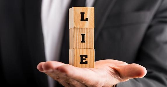 Man holding wooden blocks that spell out 'LIE' © iStock.com/Gajus