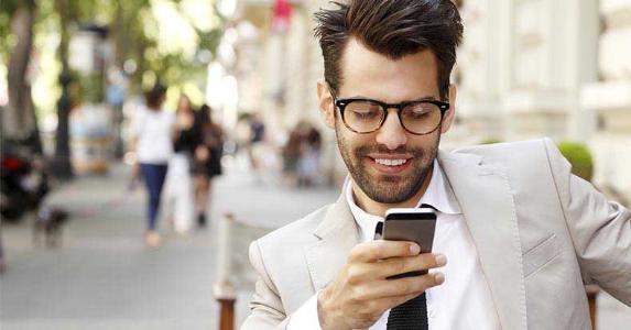 Man wearing beige suit, browsing smartphone | Kinga/Shutterstock.com