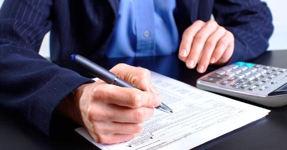 Man in blue jacket filling up tax return form © docent/Shutterstock.com