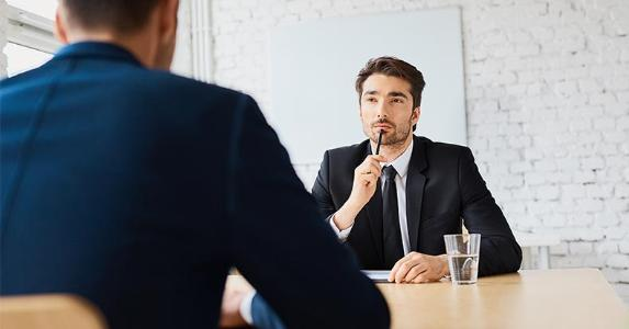 Man in suit, thinking during an interview | baranq/Shutterstock.com