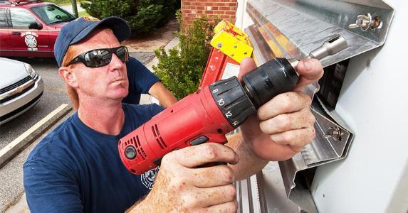 Installing hurricane shutters | PAUL J. RICHARDS/Getty Images