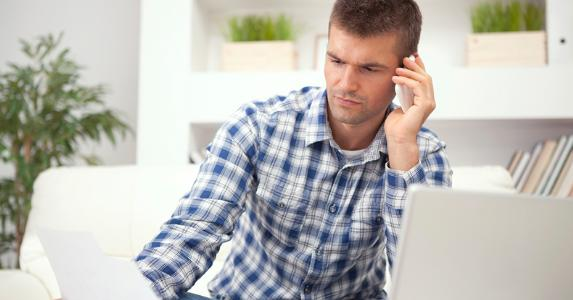 Man calling services over paperwork © iStock