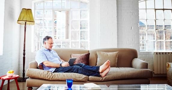 Man reading book on his couch | Kelvin Murray/Getty Images