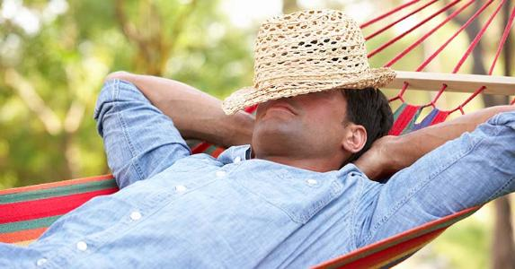 Man relaxing in hammock with hat over head © Monkey Business Images/Shutterstock.com
