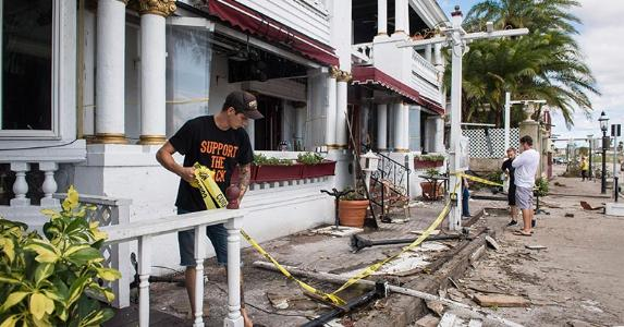 Man removing yellow caution tape from damaged home   The Washington Post/Getty Images