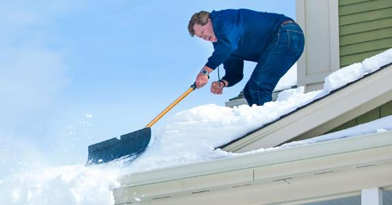 Man shoveling snow off of roof | iStock.com/Diane Diederich