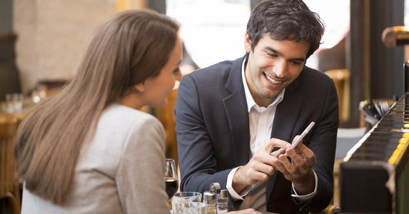 Man showing woman something on phone © LDprod/Shutterstock.com