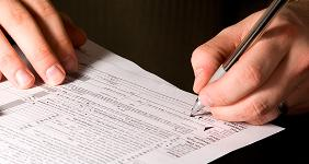 Man signing tax form  Mehmet Dilsiz - Fotolia.com