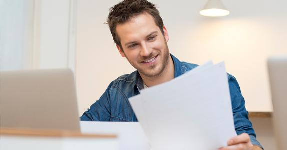Man smiling over his papers | iStock.com