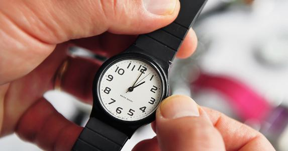 Man turning dial on wristwatch © ChameleonsEye/Shutterstock.com