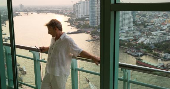 Man using his phone on hotel balcony | iStock.com/AscentXmedia