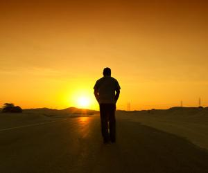 Man walking on a road with the sun setting ahead of him © Naufal MQ/Shutterstock.com