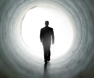Man walking through dark tunnel towards the light | joshblake/Vetta/Getty Images