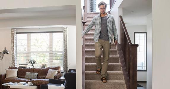 Man with book going down the stairs | Hero Images/Getty Images