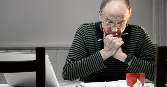 Man working on finances in his kitchen | iStock.com/Fertnig