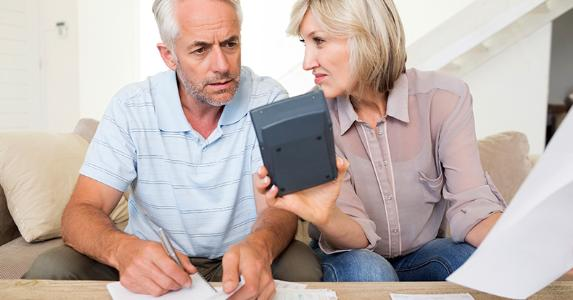 Mature couple computing budget in living room © iStock