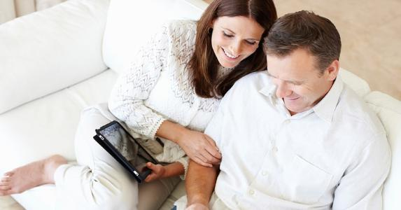 Mature couple on couch, smiling
