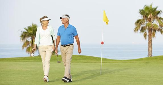 Mature couple playing golf | Chris Ryan/Getty Images