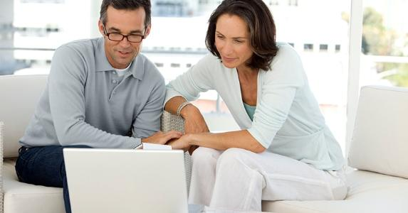 Mature couple reviewing finances on computer living room © iStock
