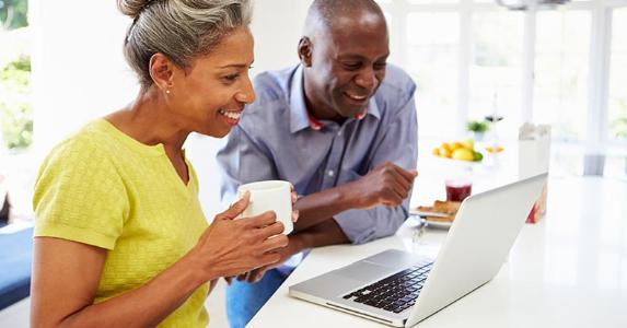 Mature couple using laptop in breakfast bar at home © Monkey Business Images/Shutterstock.com