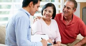 Mature Hispanic American couple with young financial adviser © Monkey Business Images/Shutterstock.com