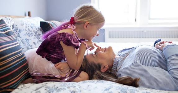 Mature lady and young girl playing in the bedroom | Jon Ragel/Getty Images