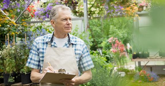 Mature man holding notes in garden | Hero Images/Getty Images