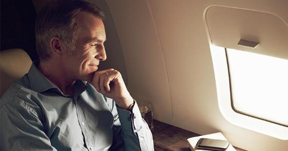 Mature man looking out the plane window | Flashpop/Getty Images