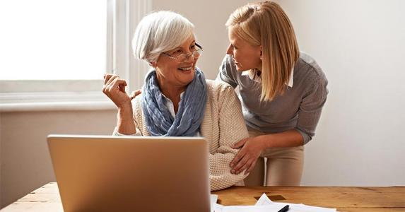Mature woman using laptop, laughing with adult daughter © PeopleImages.com/Shutterstock.com