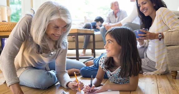 Mature woman drawing with little girl in living room floor | Hero Images/Getty Images