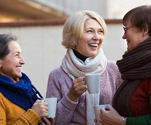 Mature women wearing sweaters, talking and drinking coffee © Iakov Filimonov/Shutterstock.com
