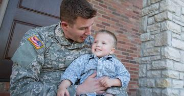 Military father holding his son on lap | Veterans United