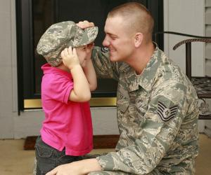 Military father putting hat on his child | JaniceRichard/E+/Getty Images